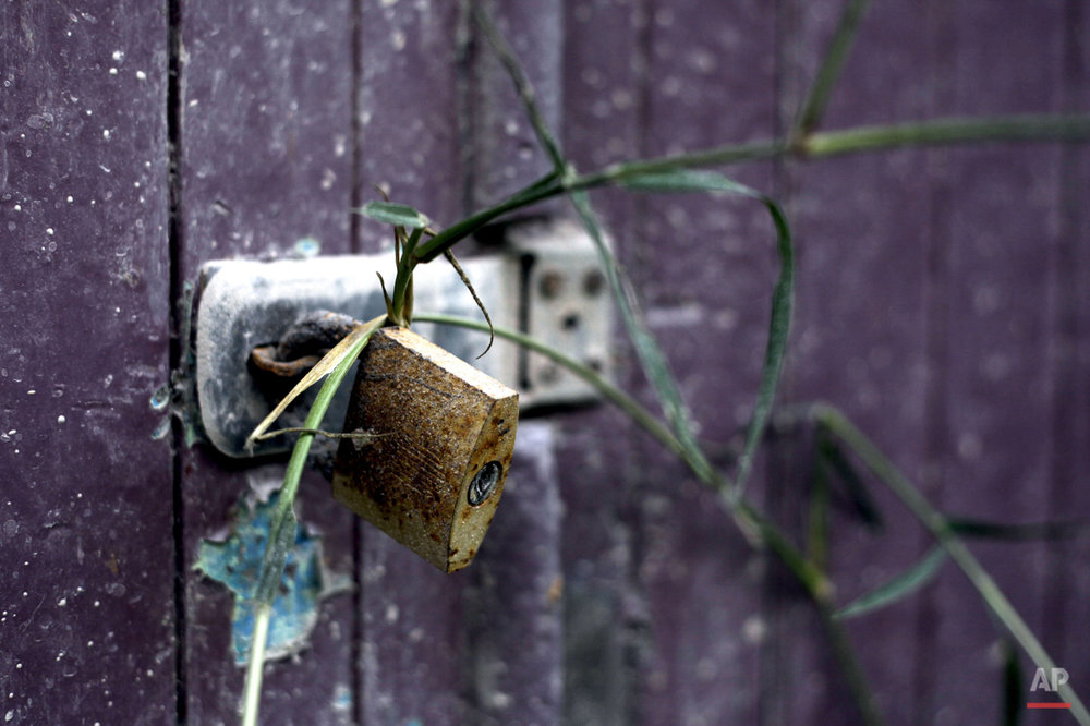 In this Friday, Nov. 13, 2015 photo, the door of a barn is seen secured with a weathered padlock in the village of Guru Kinayan which was abandoned following the eruption of Mount Sinabung, in North Sumatra, Indonesia. Crumbling buildings and personal belongings left behind now serve as eerie reminders of how life suddenly stopped when the volcano erupted and everyone was forced to evacuate their homes. (AP Photo/Binsar Bakkara)