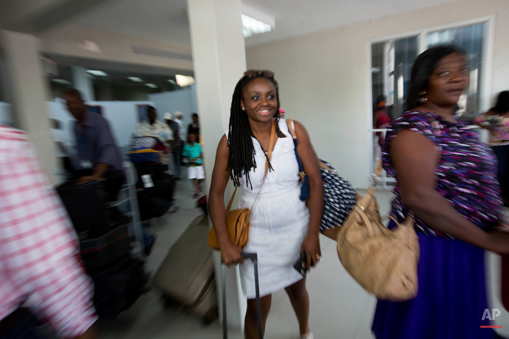 In this July 13, 2015 photo, Mariette Williams arrives in her birth country, at the Toussaint Louverture International Airport in Port-au-Prince, Haiti. Taken from Haiti by her adoptive parents in 1986, the trip to Haiti was about seeing her biological mother for the first time in nearly 30 years. (AP Photo/Dieu Nalio Chery)