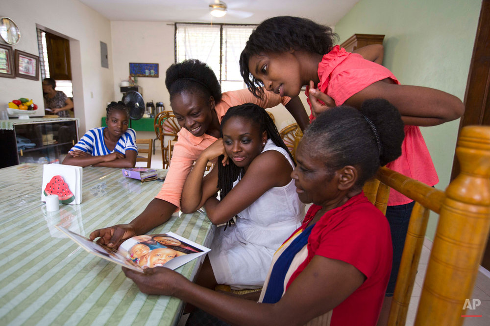 In this July 13, 2015 photo, Mariette Williams, center in white, watches as her mother Colas Etienne, from right, niece Tamaica, and sister Aliette, look at images of Mariette's children and husband, in Port-au-Prince, Haiti. A Florida teacher with a master's degree, Mariette thought that she was adopted because her parents were too poor to take care of her. But through social media she found a sister and learned that her parents had not consented to the adoption. (AP Photo/Dieu Nalio Chery)