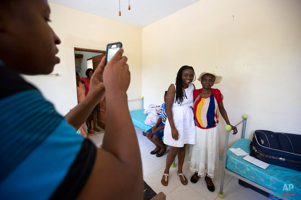 In this July 13, 2015 photo, Mariette Williams poses for a photo with her birth mother Colas Etienne, in Port-au-Prince, Haiti. Colas was a shadow at the very edge of Mariette's memories, a daughter who had been adopted by a Canadian couple in 1986. Through social media Mariette found Colas, the mother she never knew. (AP Photo/Dieu Nalio Chery)