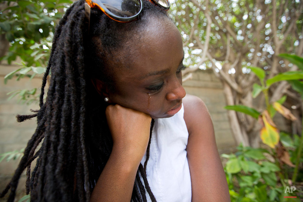 In this July 13, 2015 photo, Mariette Williams cries as she waits to see her birth mother and other family members for the first time in nearly 30 years, in Port-au-Prince, Haiti. She was surprised, and a little annoyed, that her Haitian relatives werenít at the airport. After a half-hour drive through the dusty streets, she arrived at the guest house where she had booked rooms for her family for the week. They werenít there either. (AP Photo/Dieu Nalio Chery)