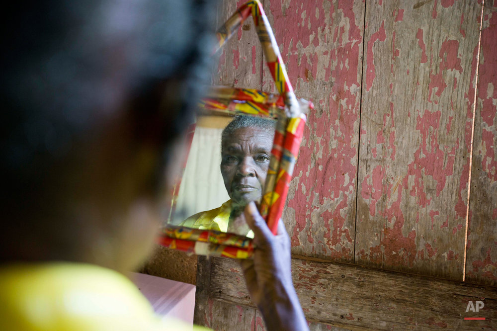 ADVANCE FOR FRIDAY, NOV. 27, 2015, AND THEREAFTER - In this July 15, 2015 photo, Colas Etienne looks at her reflection inside her home in Deron, a neighborhood on the outskirts of Pestel, Haiti. Colas Etienne was a shadow at the very edge of Mariette William's memories, a daughter who had been adopted by a Canadian couple in 1986. Through social media Mariette found Colas, the mother she never knew. (AP Photo/Dieu Nalio Chery)