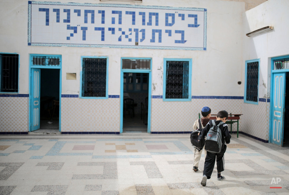 In this Friday, Oct. 30, 2015 photo, boys walk inside a Talmudic school at  Hara Kbira, the main Jewish neighborhood on the Island of Djerba, southern Tunisia. When school lets out, the streets around the ancient synagogue on this Tunisian island fill with rambunctious boys wearing Jewish kippahs and girls in long skirts, shouting to each other in Hebrew, Arabic and French. (AP Photo/Mosa'ab Elshamy)