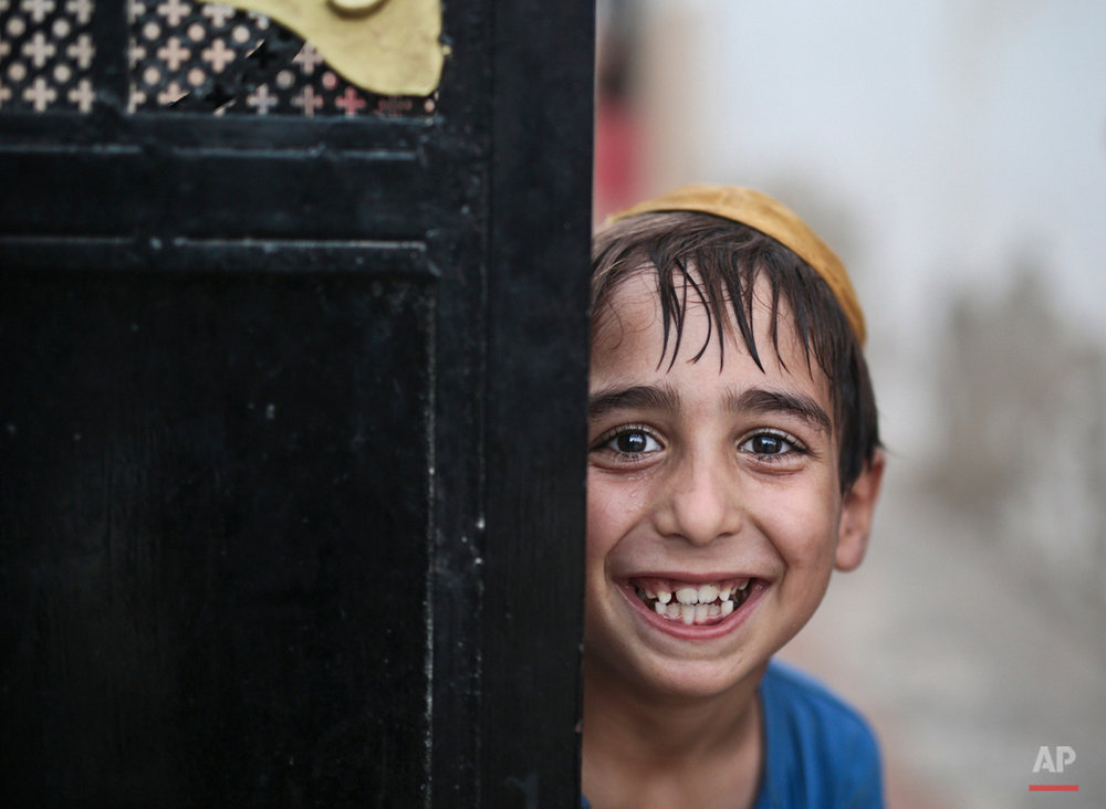 In this Thursday, Oct. 29, 2015 photo, a student covering his head with a Kippah poses for the camera as he leaves the main Talmudic school at Hara Kbira, the main Jewish neighborhood on the Island of Djerba, southern Tunisia. Tunisiaís Jewish population has dwindled from 100,000 in 1956, when the country won independence from France, to less than 1,500, mainly as a result of emigration to France and Israel. But unlike in much of the rest of the Arab world, Tunisian Jews have seen little direct persecution and have only rarely been targeted by extremists. (AP Photo/Mosa'ab Elshamy)