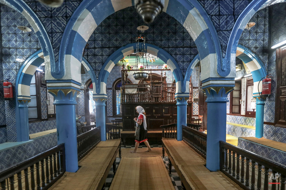 In this Wednesday, Oct. 28, 2015 photo, a tourist visits La Ghriba, the oldest synagogue in Africa, on the Island of Djerba, southern Tunisia. Beneath intricate tile walls bearing blue and yellow geometric shapes that would not seem out of place at a mosque. The synagogueís name can be translated as ìstrangeî or ìmiraculous.î (AP Photo/Mosa'ab Elshamy)