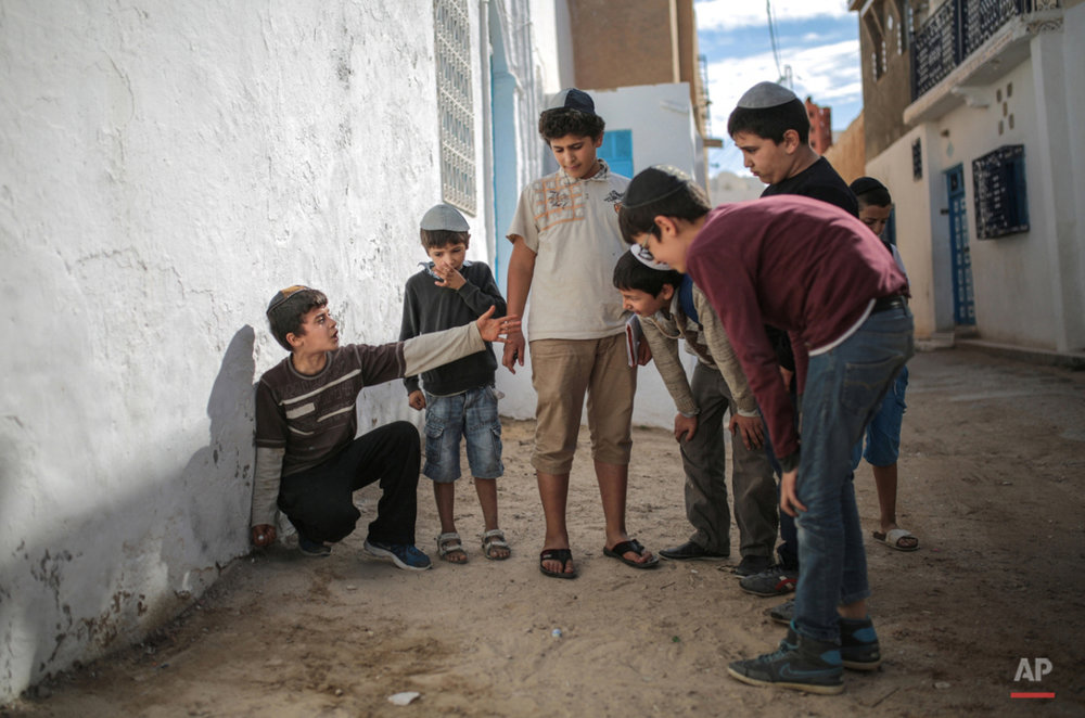In this Friday, Oct. 30, 2015 photo, boys play with marbles outside their school at Hara Kbira, the main Jewish neighborhood in the Island of Djerba, southern Tunisia. The Jewish community on the resort island of Djerba traces its roots all the way back to Babylonian exile of 586 B.C., and is one of the few communities of its kind to have survived the turmoil around the creation of Israel, when more than 800,000 Jews across the Arab world either emigrated or were driven from their homes. (AP Photo/Mosa'ab Elshamy)