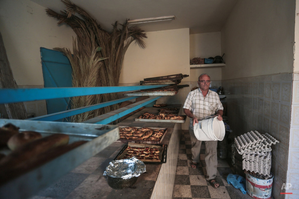 In this Friday, Oct. 30, 2015 photo, Yofel Sabbagh, 46, walks inside a bakery as he prepares Challah, a special Jewish bread, on the eve of Shabbath, at Hara Kbira, the main Jewish neighborhood on the Island of Djerba, southern Tunisia. The Jewish community in the resort island of Djerba traces its roots all the way back to Babylonian exile of 586 B.C., and is one of the few communities of its kind to have survived the turmoil around the creation of Israel, when more than 800,000 Jews across the Arab world either emigrated or were driven from their homes. (AP Photo/Mosa'ab Elshamy)