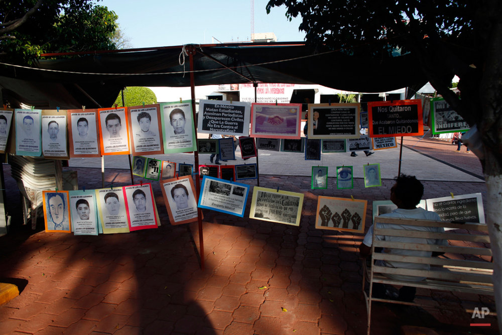 In this Oct. 1, 2015 photo, a man sits next to a permanent installation memorializing the 43 missing students, outside of the municipal palace in the city of Iguala, Mexico. The disappearance of 43 students at the hands of Iguala police on Sept. 26, 2014 began to unveil the scope of police involvement in Mexicoís nearly 26,000 recorded disappearances. Amid national outrage over the studentsí abduction, hundreds of families came forward to report their missing relatives, many of them also with the complicity of police. (AP Photo/Dario Lopez-Mills)