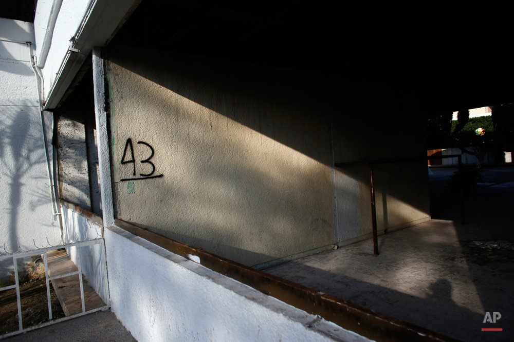 This Oct. 1, 2015 photo shows the number 43 spray painted on a wall of the partially destroyed municipal palace in Iguala, Mexico. The government building was torched by protesters last year in the aftermath of the disappearance of the 43 students on Sept. 26, 2014. A government investigation into the studentsí disappearance stated that a top commander of Igualaís police managed the Guerreros Unidos drug cartelís police payroll, from the mafia to members of the force. The same commander also oversaw police roadblocks at all of the highway entrances to Iguala--roadblocks that ensured drug loads moved through, that suspected enemies of the cartel were intercepted, and that kidnappers were free to bag their prey. (AP Photo/Dario Lopez-Mills)