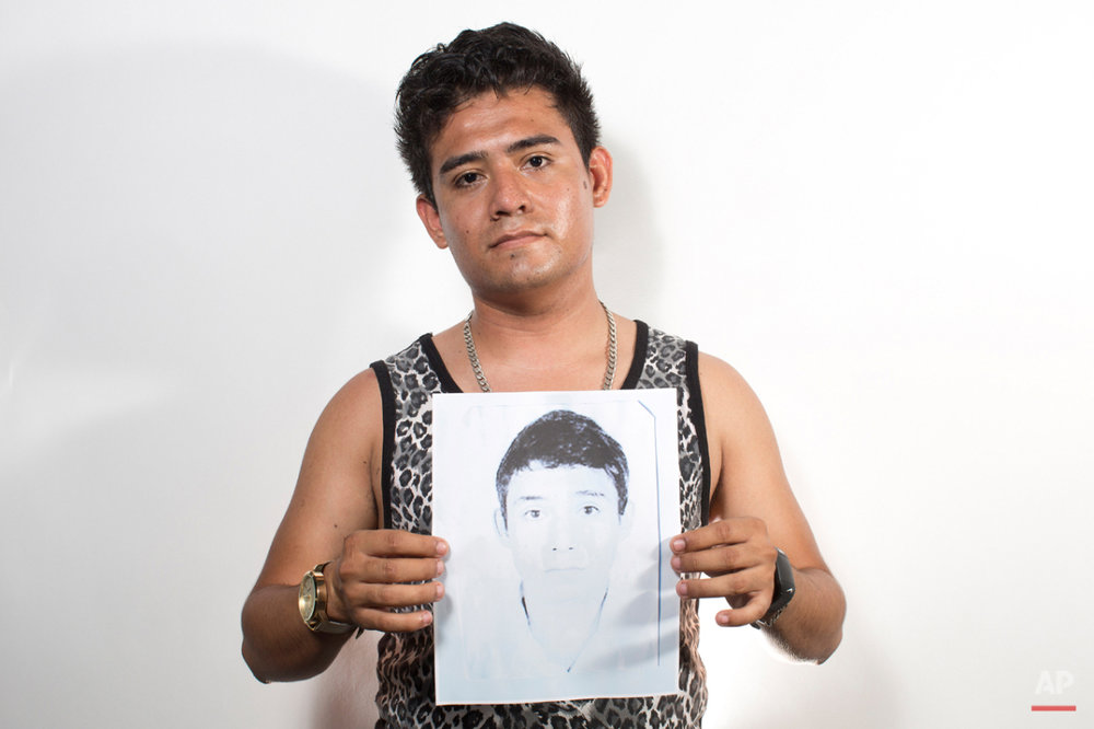 In this Aug. 18, 2015 photo, Marcos Javier Mejia Mazon holds up a photo of his brother, Angel Alberto Mejia Mazon, in Iguala, Mexico. Angel Alberto was at Igualaís annual fair in February 2013 with a group of friends when he got into a fight with a stranger. Suddenly an Iguala police truck pulled up and arrested Angel Alberto, a 19-year-old student and waiter. The other guy was let go. His friends suspected he had simply tangled with the wrong stranger. His grandfather went to the police station to look for him, but was told they had no record of his arrest. (AP Photo/Dario Lopez-Mills)