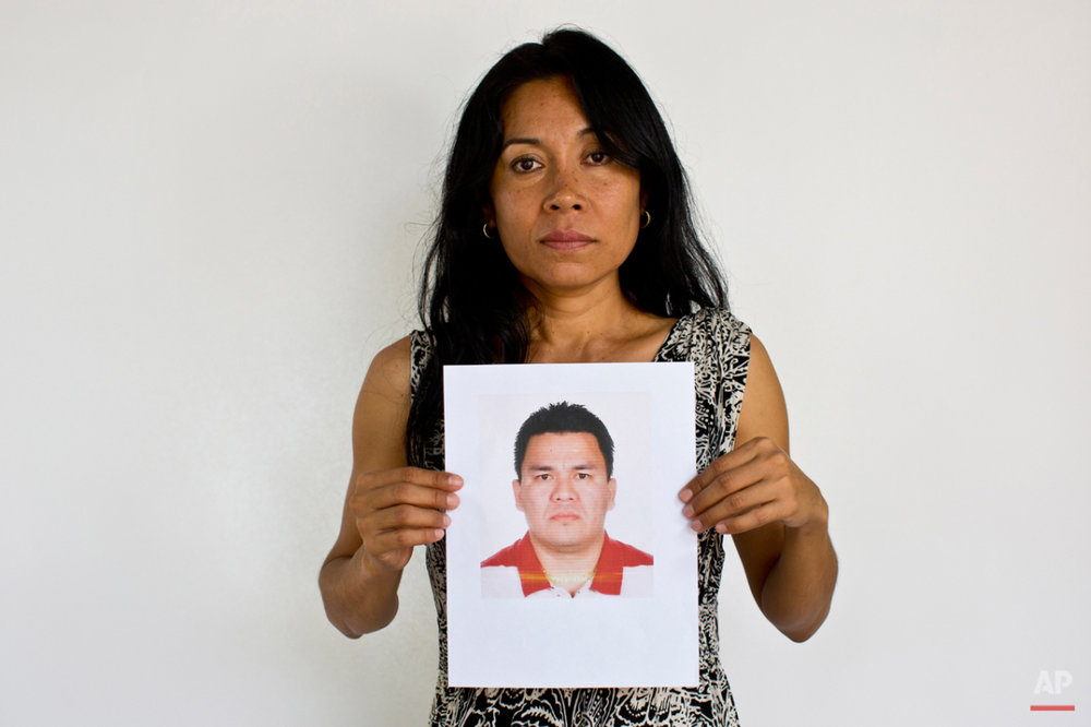 In this May 13, 2015 photo, Adriana Bahena Cruz holds up a photo of her husband, Saulo Rodriguez Cruz, in Iguala, Mexico. Bahena's husband was a detective with the state prosecutorís office in Iguala. On Jan. 7, 2011, he was in downtown Iguala with his wife and children when he received a call saying there was a development in one of his cases and he needed to come into the office. His wife awoke at 2 a.m. to find he was still not home. When she called him he answered, but she heard the voices of a lot of other men in the background. He said he would be home soon. She never heard from him again. (AP Photo/Dario Lopez-Mills)