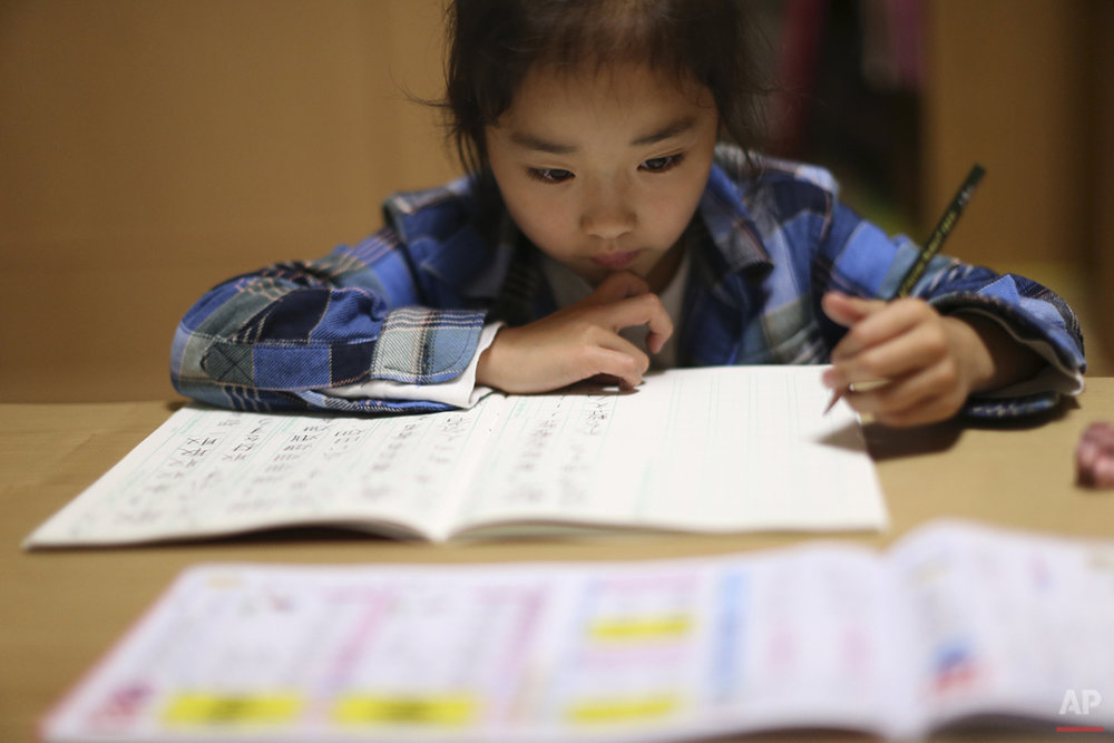 "In this Nov. 18, 2015 photo, 9-year-old Mahiro Takano, three-time Japan karate champion in her age group, does her school homework's at home before going to her karate practice in Nagaoka, Niigata Prefecture, north of Tokyo.  Mahiro stars in singer Sia's latest music video ""Alive,"" the just-released single from the singer's upcoming album. (AP Photo/ Eugene Hoshiko)"
