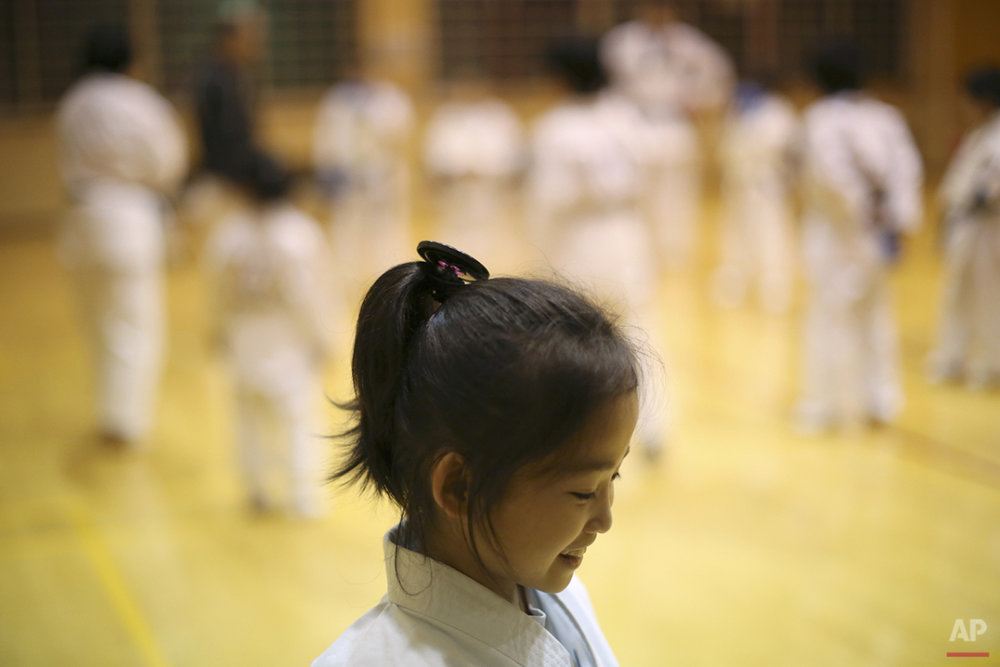 "In this Nov. 18, 2015 photo, 9-year-old Mahiro Takano, three-time Japan karate champion in her age group smiles during her karate practice in Nagaoka, Niigata Prefecture, north of Tokyo. Mahiro stars in singer Sia's latest music video ""Alive,"" the just-released single from the singer's upcoming album. She has a soft spot for Duffy the Disney Bear and her favorite food is chocolate. She does her homework before dinner, but what she really loves are skateboarding, playing video games and bouncing on her trampoline. (AP Photo/Eugene Hoshiko)"