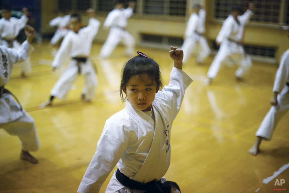 "In this Nov. 18, 2015 photo, 9-year-old Mahiro Takano, center, three-time Japan karate champion in her age group practices in Nagaoka, Niigata Prefecture, north of Tokyo.  Mahiro stars in singer Sia's latest music video ""Alive,"" the just-released single from the singer's upcoming album. (AP Photo/Eugene Hoshiko)"