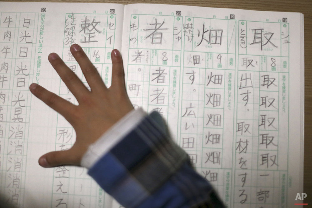 "In this Nov. 18, 2015 photo, 9-year-old Mahiro Takano, three-time Japan karate champion in her age group does her homework of Japanese letters Kanji before going to her practice of karate at home in Nagaoka, Niigata Prefecture, north of Tokyo. Mahiro stars in singer Sia's latest music video ""Alive,"" the just-released single from the singer's upcoming album. (AP Photo/ Eugene Hoshiko)"