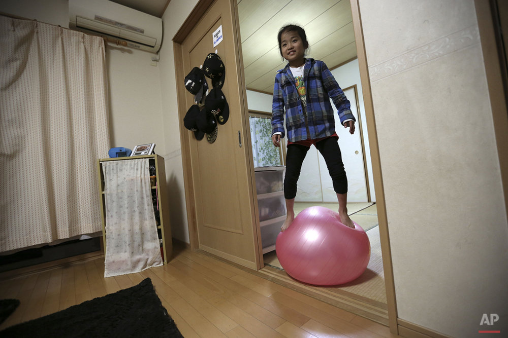 "In this Nov. 18, 2015 photo, 9-year-old Mahiro Takano, three-time Japan karate champion in her age group plays with a balance ball before going to her practice of karate at home in Nagaoka, Niigata Prefecture, north of Tokyo. Mahiro stars in singer Sia's latest music video ""Alive,"" the just-released single from the singer's upcoming album. She has a soft spot for Duffy the Disney Bear and her favorite food is chocolate. She does her homework before dinner, but what she really loves are skateboarding, playing video games and bouncing on her trampoline. (AP Photo/ Eugene Hoshiko)"