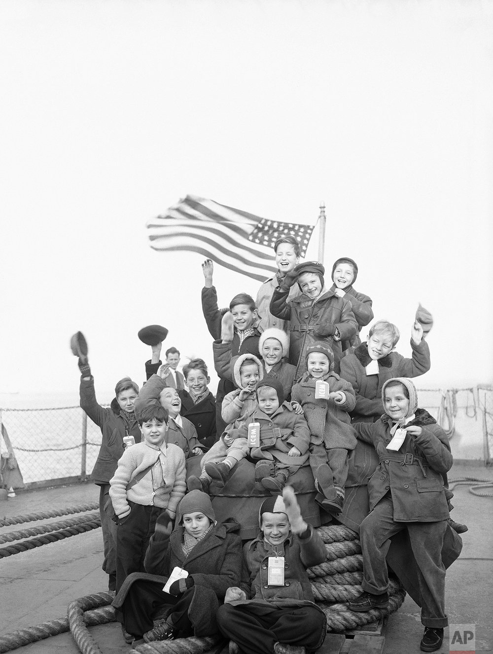 A happy group of Hungarian youngsters needs no prompting to smile for the photographer for this pose aboard the Navy transport Gen. Walker which brought nearly 2,000 Hungarians to New York Feb.15, 1957. They were a part of the largest group of refugees to arrive in the United States through the Government's sea-lift. After docking, they were transported to Camp Kilmer, N.J., for processing. (AP Photo/Anthohny Camerano)