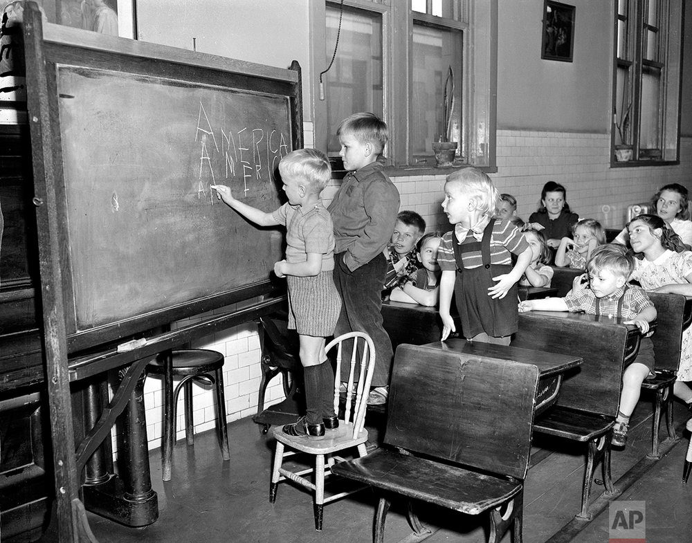 """In this April 7, 1949 photo, three Finnish children write """"America"""" on a chalkboard in a class held for children of immigrants detained at Ellis Island in New York City. They range in ages 3 to 11 years old. The American self-image is forever intertwined with the melting pot _ a nation that embraces the world's wretched refuse, a nation built by immigrants. But America's immigration history is complicated. (AP Photo)"""