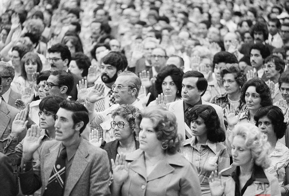 Part of a group 17,1941 persons take the oath of allegiance to the U.S. and become citizens in one of the largest naturalization ceremonies in history, Sunday, July 5, 1976, Miami Beach, Fl. The people in the photograph are unidentified. (AP Photo/BH)