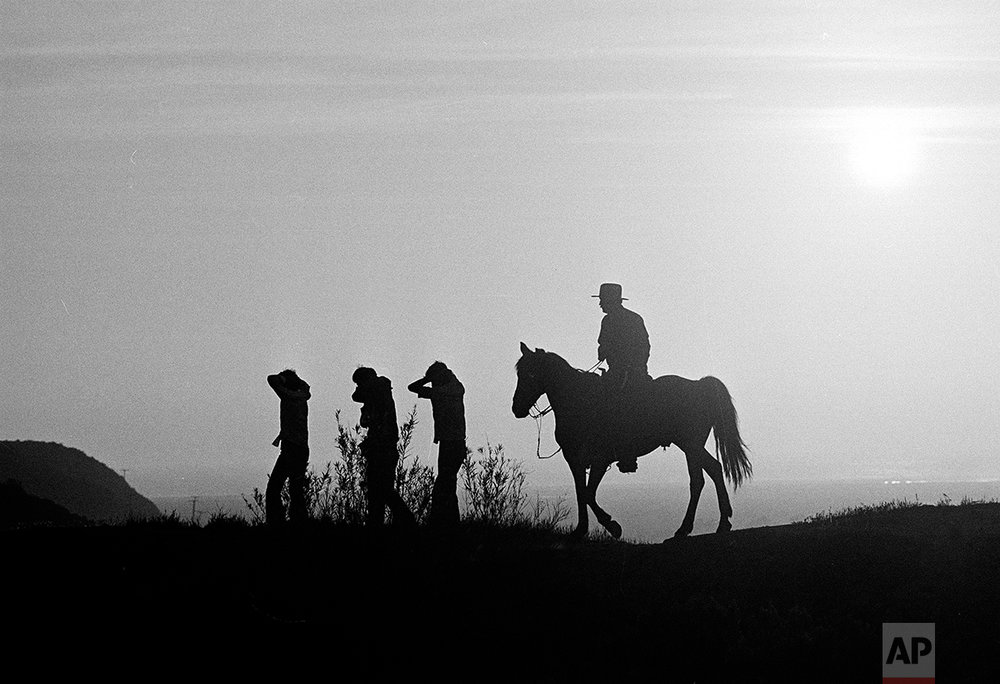 U.S. Border Patrol officer Ed Pyeatt, on horseback, leads a group of illegal aliens down the hillside toward waiting vans for the trip to a holding center at the Chula Vista border station. According to Pyeatt, a monthly average of 10, 000 illegals are captured in this 6-mile stretch of border, Aug. 18, 1981. (AP Photo)
