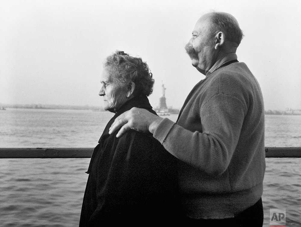 In this Oct. 28, 1956 photo, Mr. and Mrs. Paul Roerich from Bavaria, Germany, look out from the stern of the USNS General Langfitt anchored in New York Harbor carrying 1,267 refugees from Europe. In the background is the Statue of Liberty. The couple plan to settle in Ohio. The American self-image is forever intertwined with the melting pot _ a nation that embraces the world's wretched refuse, a nation built by immigrants. But America's immigration history is complicated. (AP Photo)