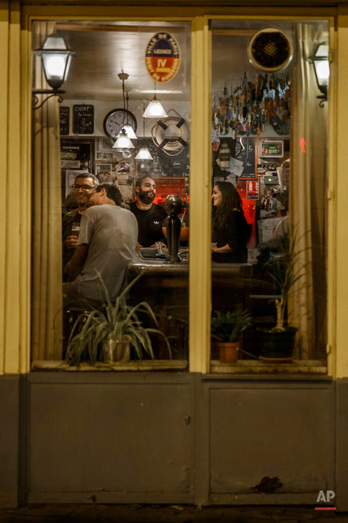 In this Nov. 17, 2015 picture people enjoy dinner at 'La Plage' close to one of the spots of Friday's attacks in Paris. Parisians are returning to cafes, bars and restaurants, determined that the Nov. 13 attacks won't alter the city's way of life. President Francois Hollande has told his compatriots that 'life must resumed in full,' asking: 'What would our country be without its cafes?'(AP Photo/Daniel Ochoa de Olza)