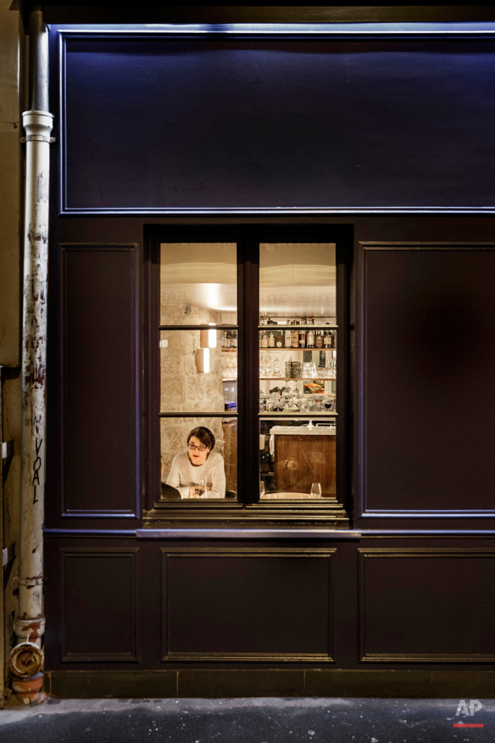 In this Nov. 17, 2015 picture a woman enjoy dinner at 'Pizza, pour emporter' close to one of the spots of Friday's attacks in Paris. Parisians are returning to cafes, bars and restaurants, determined that the Nov. 13 attacks won't alter the city's way of life. President Francois Hollande has told his compatriots that 'life must resumed in full,' asking: 'What would our country be without its cafes?'(AP Photo/Daniel Ochoa de Olza)