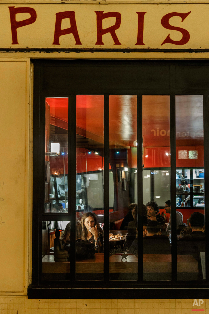In this Nov. 17, 2015 picture people enjoy dinner at 'Paris - Hanoi' close to one of the spots of Friday's attacks in Paris. Parisians are returning to cafes, bars and restaurants, determined that the Nov. 13 attacks won't alter the city's way of life. President Francois Hollande has told his compatriots that 'life must resumed in full,' asking: 'What would our country be without its cafes?'(AP Photo/Daniel Ochoa de Olza)