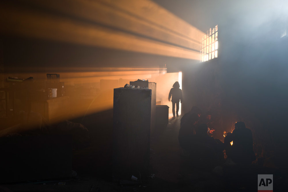 A group of migrants warm themselves by a fire in an abandoned warehouse in Belgrade, Serbia, Monday, Jan. 30, 2017. Hundreds of migrants have been sleeping in freezing temperatures in downtown Belgrade looking for ways to cross the heavily-guarded EU borders. (AP Photo/Muhammed Muheisen)