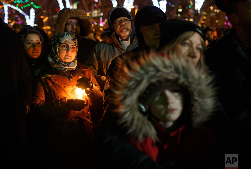 People gather in remembrance of the victims of Sunday's shooting at a Quebec City mosque, during a vigil in Edmonton, Alberta, Monday, Jan. 30, 2017. A French Canadian known for far-right, nationalist views was charged with six counts of first-degree murder and five counts of attempted murder over the shooting rampage at the mosque that Canada's prime minister called an act of terrorism against Muslims. (Jason Franson/The Canadian Press via AP)