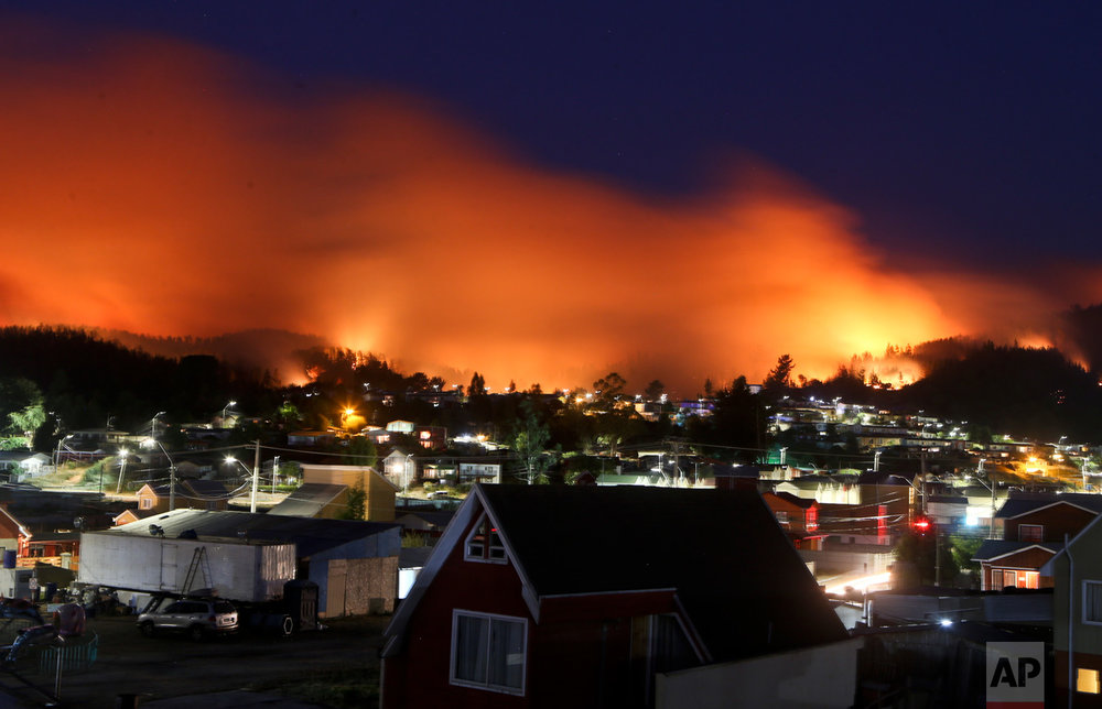 A wildfire approaches Chile's Dichato community, Monday, Jan. 30, 2017, where firefighters are working to keep the flames away from the estimated 800 homes. The fires have consumed forests, livestock and entire towns, prompting President Michelle Bachelet to declare a state of emergency, deploy troops and ask for international help. (AP Photo/Esteban Felix)