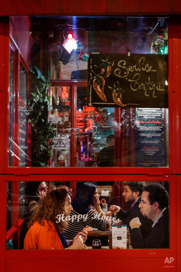 In this Nov. 17, 2015 picture a people enjoy dinner at  'Le Petit Baiona' restaurant close to one of the spots of Friday's attacks in Paris.. Parisians are returning to cafes, bars and restaurants, determined that the Nov. 13 attacks won't alter the city's way of life. President Francois Hollande has told his compatriots that 'life must resumed in full,' asking: 'What would our country be without its cafes?'(AP Photo/Daniel Ochoa de Olza)
