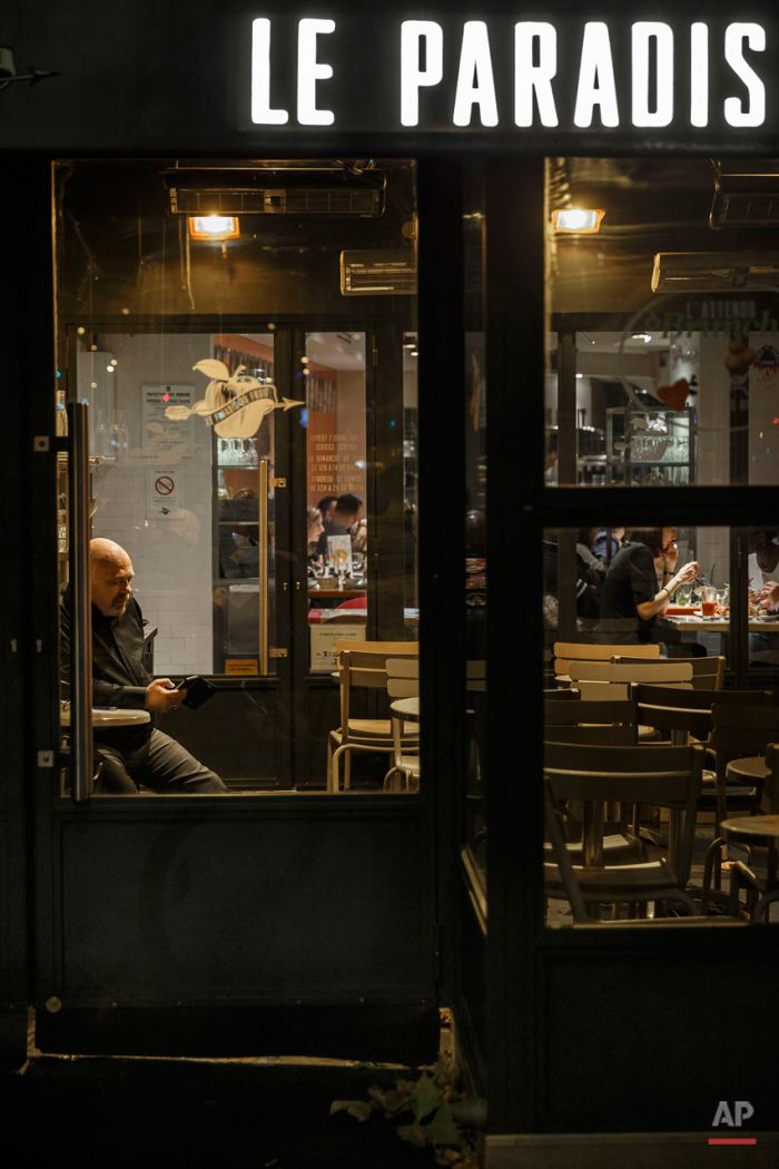 In this Nov. 17, 2015 picture people enjoy dinner at 'Le Paradis' close to one of the spots of Friday's attacks in Paris. Parisians are returning to cafes, bars and restaurants, determined that the Nov. 13 attacks won't alter the city's way of life. President Francois Hollande has told his compatriots that 'life must resumed in full,' asking: 'What would our country be without its cafes?'(AP Photo/Daniel Ochoa de Olza)