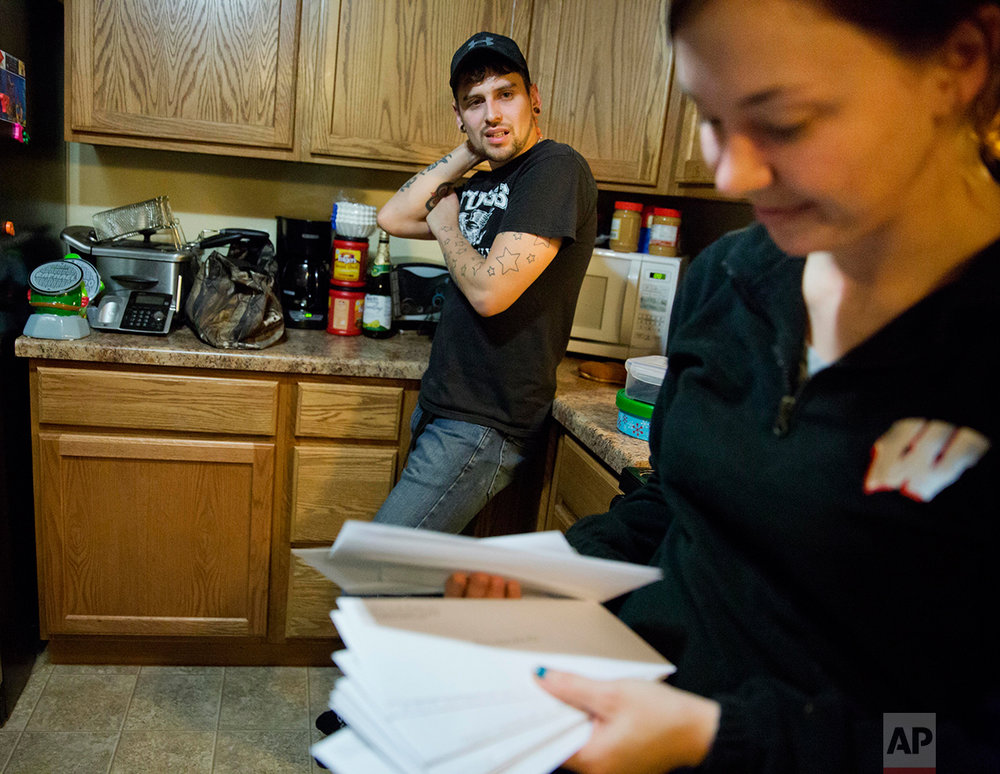 Kreig Holt, left, looks on as his wife, Lydia, flips through envelopes, each containing money for the each of the monthly bills they have to pay, as they stand in their kitchen in Wauzeka, Wis., Tuesday, Jan. 17, 2017. They both earn about $10 an hour and, with two kids, there's always one or two they have to skip. She did the math; at this rate, they'll be paying these same bills for 87 years. In 2012, Lydia Holt voted for Barack Obama because he promised her change, but she feels that change hasn't reached her here. So in 2016, she chose Donald Trump. (AP Photo/David Goldman)