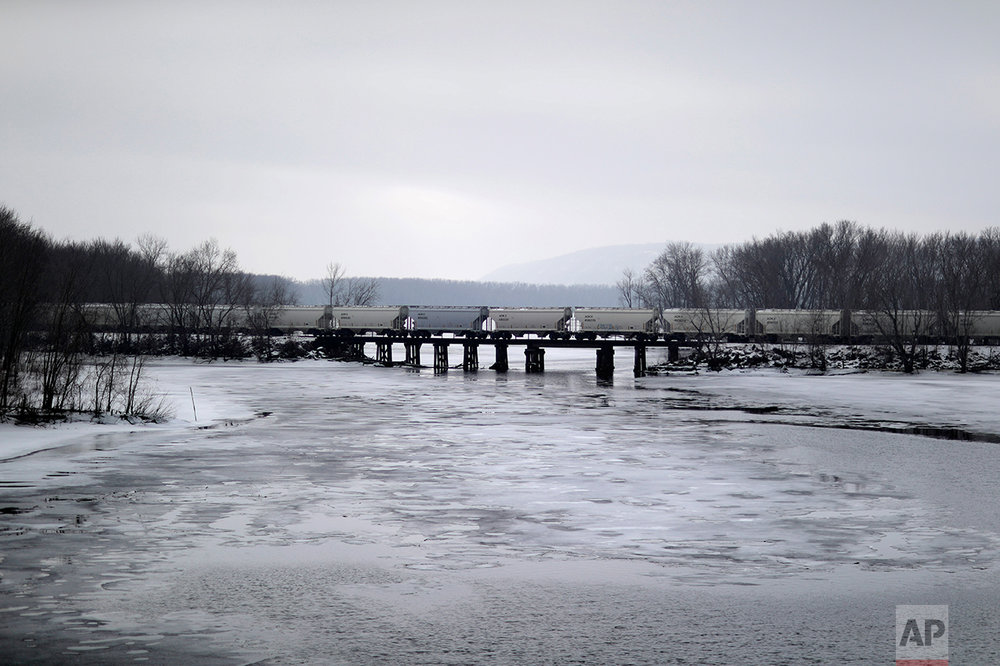 A train travels over the Mississippi River in Prairie du Chien, Wis., Wednesday, Jan. 18, 2017. So many voters switched from blue to red in some 50 counties stretching 300 miles down the Mississippi River, through Minnesota, Wisconsin, Iowa and Illinois, that it transformed in one election season into Donald Trump Country. (AP Photo/David Goldman)