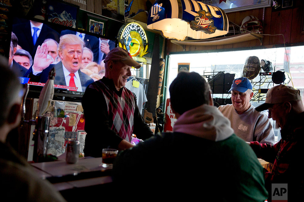 President Donald Trump is sworn in during a live broadcast of the inauguration as Denny Riebe, from right, Doug Dickman, Scott Reilly, and Bill Winter, play cards at the Sawmill Saloon in Prairie du Chien, Wis., Friday, Jan. 20, 2017. The men who meet here for cards every morning and call themselves the Corner of Superior Knowledge are made up democrats, Trump supporters and another described as agnostic. The campaign vitriol that has cleaved apart the country has not left the same scars here, a place where talking politics is considered impolite, where wives reported not knowing how their own husbands voted and husbands said they never asked their wives. (AP Photo/David Goldman)