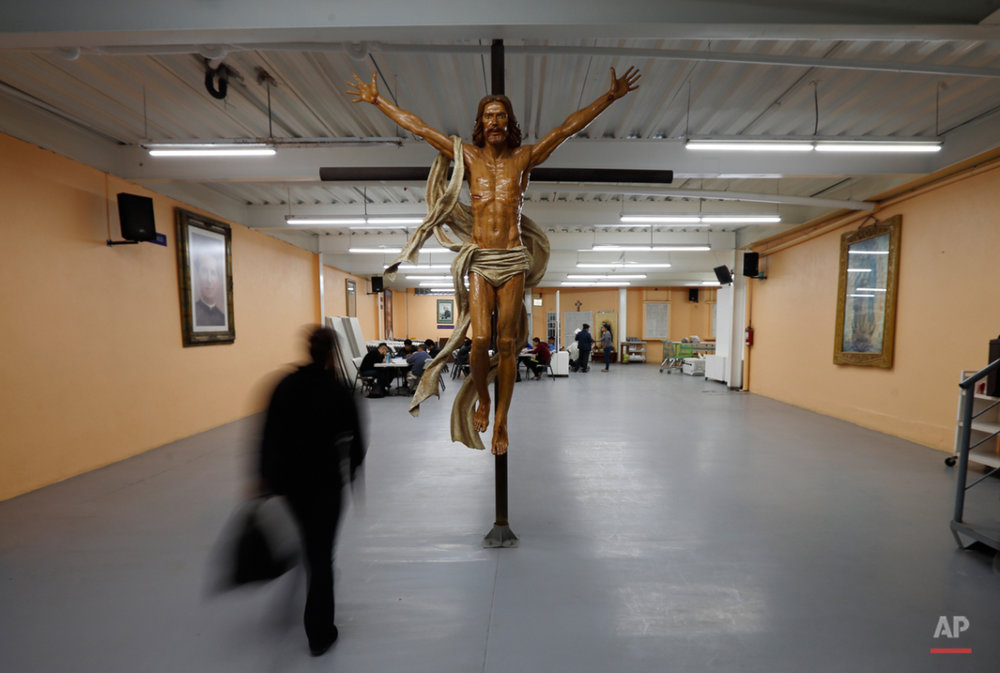 A woman passes an image of Jesus at a shelter for migrants  Wednesday, Nov. 18, 2015, in Tijuana, Mexico. A new study finds more Mexicans are leaving the United States than coming to the country, marking a reversal to one of the most significant immigration trends in U.S. history. (AP Photo/Gregory Bull)