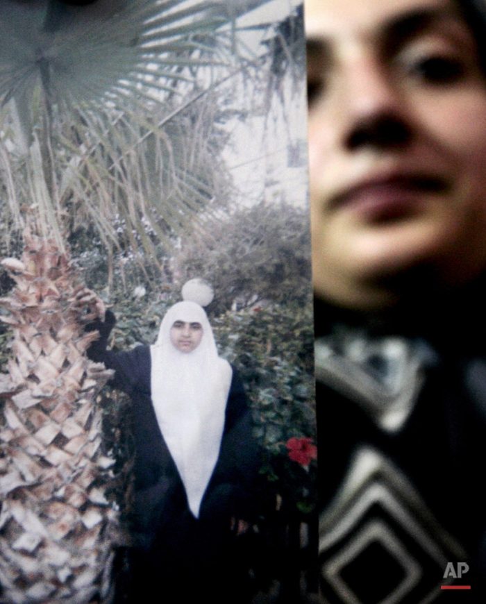 In this Monday Nov. 6, 2006 photo, an unidentified relative holds a photo of Palestinian female suicide bomber Merfat Masoud at the family house in the northern Gaza Strip town of Beit Lahiya. While most suicide bombers are men, Islamic militant groups have occasionally deployed women to carry out such attacks. Long before the rise of Islamic radicalism, women suicide bombers were used by leftist and separatist groups in the Arab and beyond. (AP Photo/Khalil Hamra)