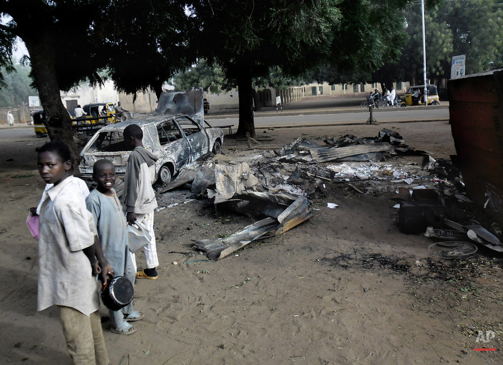 In this Monday Jan. 12, 2015 photo, Children stand near the scene of an explosion a day after two female suicide bombers targeted the busy marketplace in Potiskum, Nigeria. While most suicide bombers are men, Islamic militant groups have occasionally deployed women to carry out such attacks. Long before the rise of Islamic radicalism, women suicide bombers were used by leftist and separatist groups in the Arab and beyond. (AP Photo/Adamu Adamu)