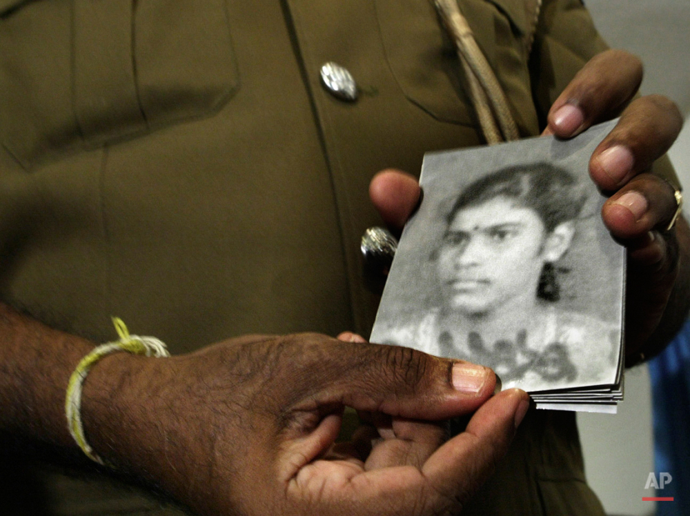 In this Friday, Nov. 30, 2007 photo, a police spokes person distributes photographs of an alleged female suicide bomber who exploded outside a senior minister's office in Colombo, Sri Lanka. While most suicide bombers are men, Islamic militant groups have occasionally deployed women to carry out such attacks. Long before the rise of Islamic radicalism, women suicide bombers were used by leftist and separatist groups in the Arab and beyond. (AP Photo/Gemunu Amarasinghe)