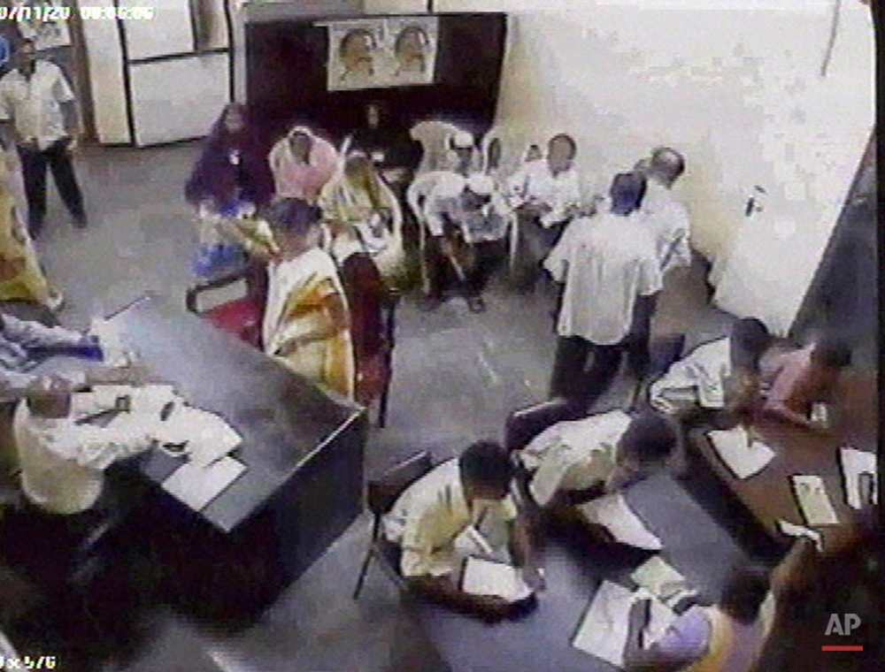 This file image made from security camera footage released by Sri Lanka police, Friday, Nov. 30, 2007, shows a female suicide bomber identified by police as 24-year-old Sujatha Vagawanam, on a mission to kill a Sri Lankan Cabinet minister. Vagawanam, center, left, standing, lifting her right hand, wearing a yellow sari and a white shawl, calmly walked into a small waiting room at the Colombo offices of Social Services Minister Douglas Devananda on Wednesday, the day he sets aside to hear complaints from members of the public. Sujatha Vagawanam, is seen here sitting in front of a desk and answered questions from Devananda's 72-year-old aide Steven Peiris, bottom, left, After nearly a minute and a half, he began gesturing for her to sit down in a nearby cluster of white plastic chairs, apparently to await a security check. She then stood up facing Peiris, reached her right hand to her right shoulder to grab something and exploded. Peiris and the bomber were both killed. (AP Photo/Sri Lanka Police via AP Televison News)