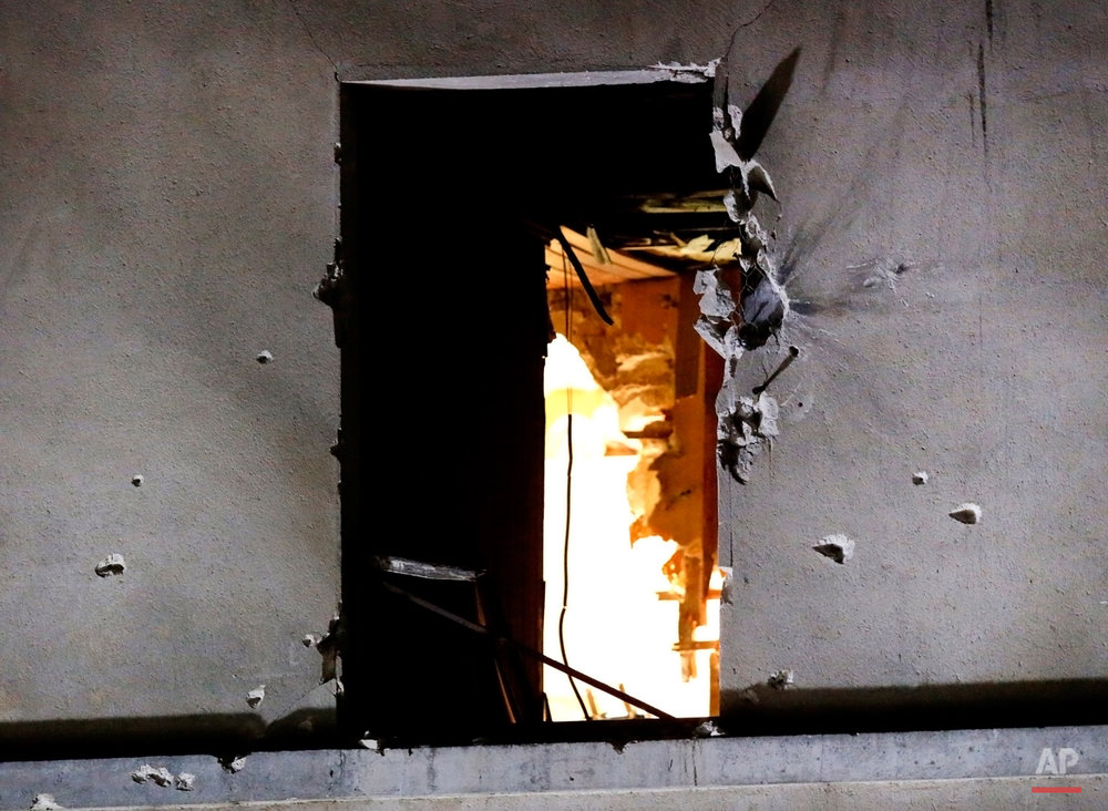 In this Wednesday, Nov. 18, 2015 photo, bullet holes are pictured around a window on the back side of the house after an intervention of security forces against a group of extremists in Saint-Denis, near Paris. A woman wearing an explosive suicide vest blew herself up Wednesday as heavily armed police tried to storm a suburban Paris apartment where the suspected mastermind of last week's attacks was believed to be holed up, police said. While most suicide bombers are men, Islamic militant groups have occasionally deployed women to carry out such attacks. Long before the rise of Islamic radicalism, women suicide bombers were used by leftist and separatist groups in the Arab and beyond. (AP Photo/Michel Euler)