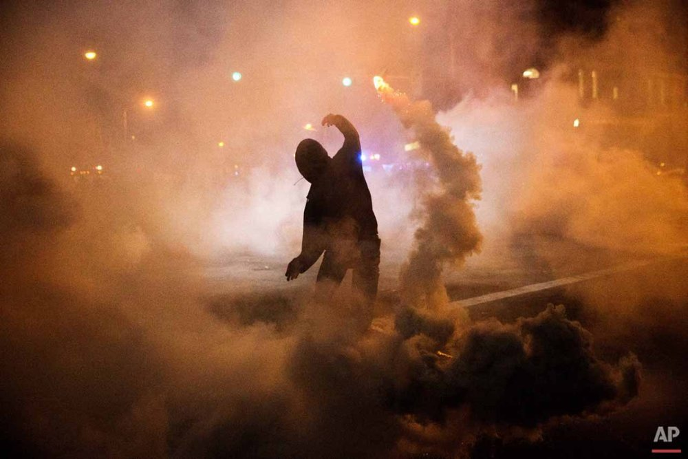A protestor throws a tear gas canister back toward riot police after a 10pm curfew went into effect in the wake of Monday's riots following the funeral for Freddie Gray, Tuesday, April 28, 2015, in Baltimore. (AP Photo/David Goldman)
