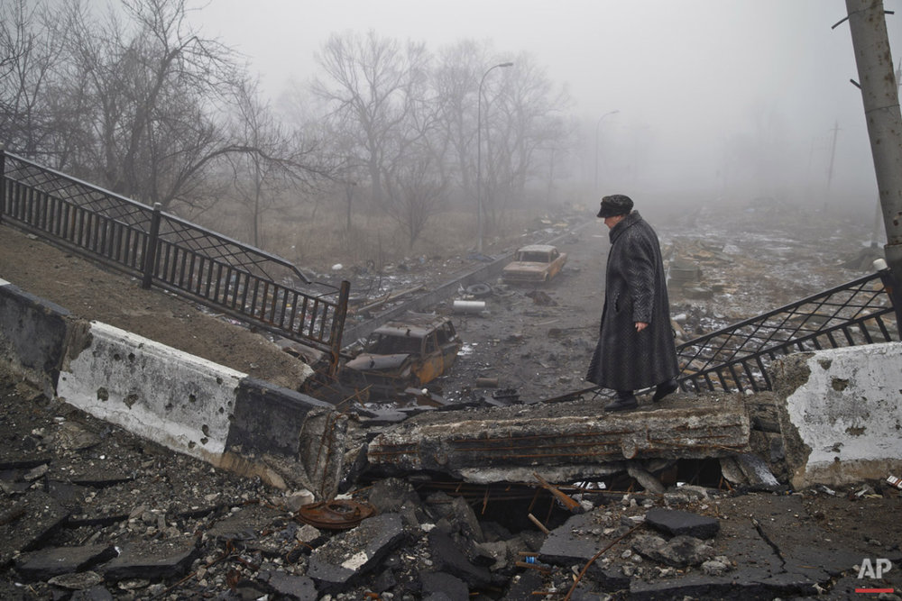 An elderly woman walks on a destroyed bridge on the road to the airport which was the scene of heavy fighting, on her way to retrieve belongings from her home, in Donetsk, Ukraine, Sunday, March 1, 2015.  (AP Photo/Vadim Ghirda)