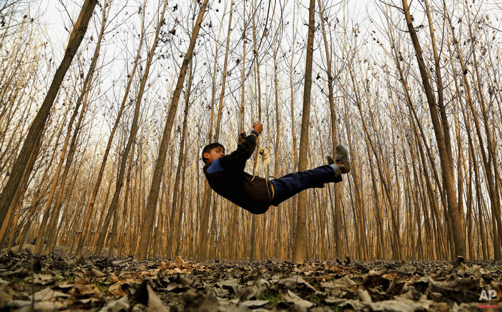 A Kashmiri boy plays on a swing in Srinagar, India, Thursday, Jan. 15, 2015. Set in the Himalayas at 5,600 feet above sea level, Kashmir is a green, saucer-shaped valley surrounded by snowy mountain ranges with over 100 lakes dotting its highlands and plains. (AP Photo/Mukhtar Khan)