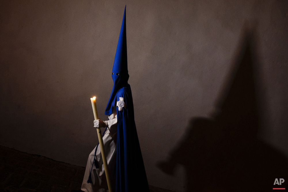 "A penitent casts his shadow as he takes part in ""Nuestro Senor Atado a la Columna, Maria Santisima de la Paz y San Juan Evangelista"" Holy Week procession in Arcos de la Frontera, Spain, Tuesday, March 31, 2015. Hundreds of processions take place throughout Spain during the Easter Holy Week.  (AP Photo/Daniel Ochoa de Olza)"