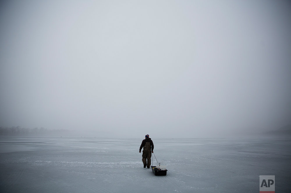 An ice fisherman walks out on a frozen portion of the Mississippi River in Prairie du Chien, Wis., Friday, Jan. 20, 2017. In this corner of middle America, in this one, small slice of the nation that sent Trump to Washington, they are watching and they are waiting, their hopes pinned on his promised economic renaissance. And if four years from now the change he pledged hasn't found them here, the people of Crawford County might change again to someone else. (AP Photo/David Goldman)