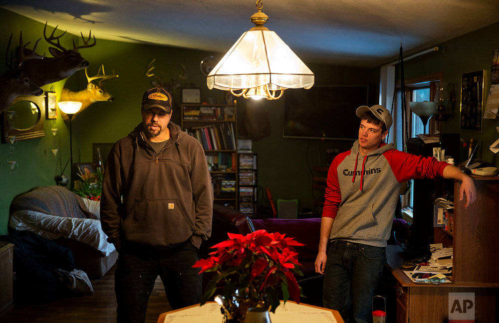 Jeff McCullick, left, stands next to his son Dylan, 18, in their home in Ferryville, Wis., Wednesday, Jan. 18, 2017. Dylan said he supported Barack Obama when he was younger and wanted his parents to vote for the first black president. But he said he's not sure he would vote for Obama as an adult. A recent high school graduate, he said he's worried about the lack of job opportunities in the county and is considering going to technical school to become a diesel mechanic. His father works in maintenance in a federal government job. (AP Photo/David Goldman)