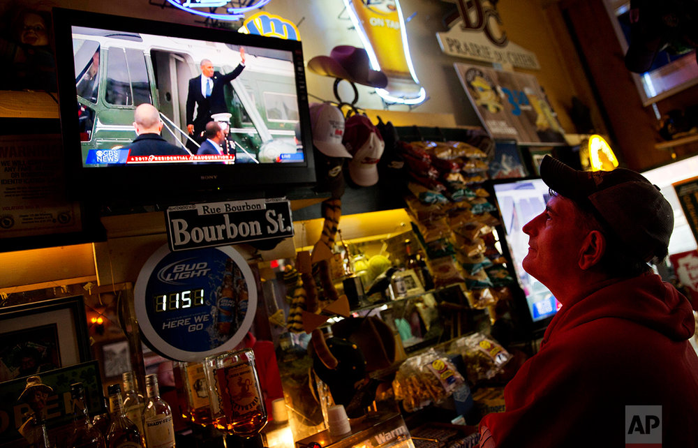 "Robbo Coleman watches a live broadcast of former President Barack Obama waving goodbye during the inauguration of President Donald Trump at the Sawmill Saloon in Prairie du Chien, Wis., Friday, Jan. 20, 2017. Coleman voted for Obama four years ago. This time, he voted for Trump. To explain why, he held up an ink pen, wrapped in plastic with ""Made in China"" printed in block letters. ""I don't see why we can't make pens in Prairie du Chien, or in Louisville, Ky., or in Alabama, or wherever,"" he said. (AP Photo/David Goldman)"