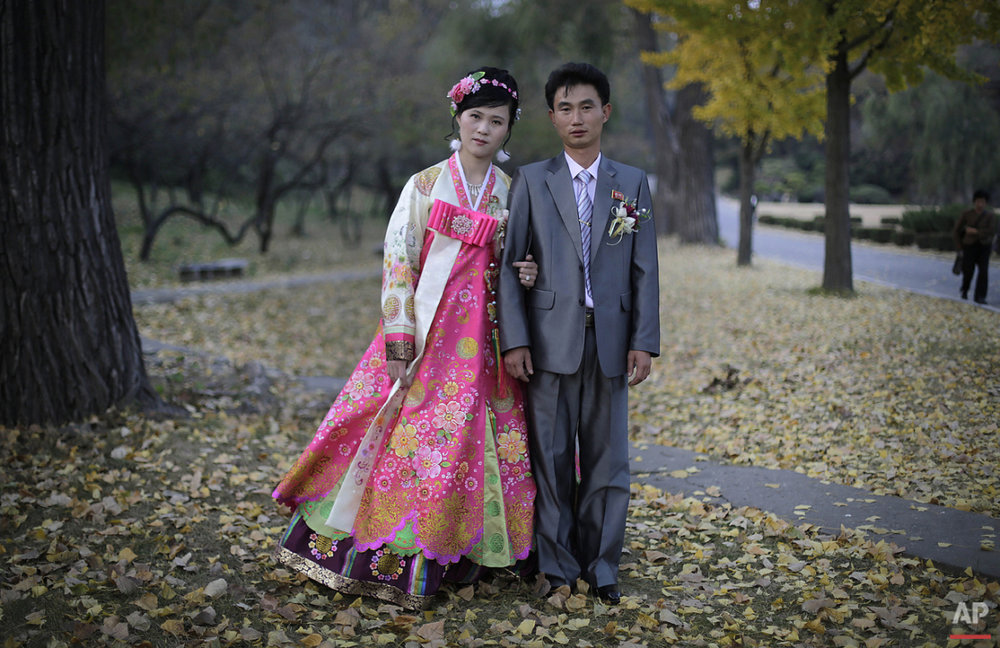 In this photo taken Saturday, Oct. 25, 2014, a North Korean bride and groom pose for a photograph at the Moranbong hill where they went to take wedding pictures, in Pyongyang, North Korea. The couple, Ri Ok Ran, 28 and Kang Sung Jin, 32, were married Saturday after dating for about two years. (AP Photo/Maye-E Wong)